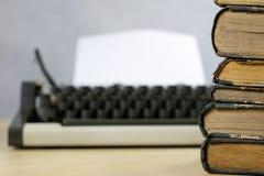 Oude boeken en schrijfmachine op een houten lijst Mening van boeken en a Stock Fotografie