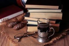 Oude boeken en thee in de avond Een glas van drank op lijst E Stock Foto's