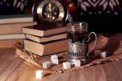 Oude boeken en thee in de avond Een glas van drank op lijst E Stock Fotografie