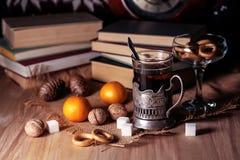 Oude boeken en thee in de avond Een glas van drank op lijst E Stock Foto
