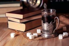 Oude boeken en thee in de avond Een glas van drank op lijst E Stock Afbeelding