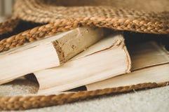 Oude boeken en uitstekende strozak op witte warme deken De zomervrouw van het zakstro Bruine met de hand gemaakte aardzak royalty-vrije stock afbeeldingen