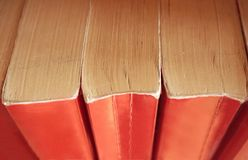 Oude boeken met rode die boekdekking verticaal op de planken wordt gestapeld Mening van hierboven royalty-vrije stock fotografie