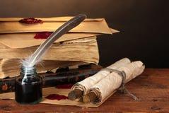 Oude boeken, rollen, veerpen en inktpot Stock Foto