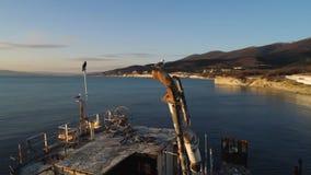 Oude boot die zich op strand bij de hemelachtergrond van de zonsondergangtijd bevinden schot Zeemeeuwen die op een gebroken schip royalty-vrije stock foto
