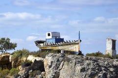 Oude boot op een rots Stock Afbeelding