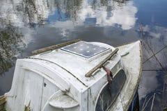 Oude boot op het kalme water met bezinning van blauwe hemel Stock Foto