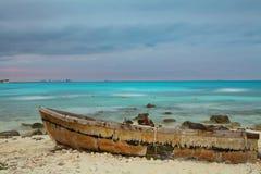 Oude boot op het strand bij zonsondergang Stock Foto's