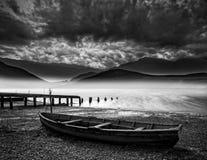 Oude boot op meer van kust met nevelige meer en bergen landscap Stock Foto's