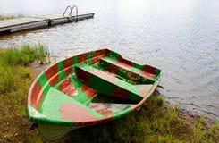 Oude boot op strand in regen Stock Foto