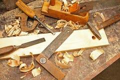 Oude bouwhulpmiddelen op de werkbank Stock Foto's