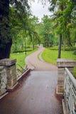 Oude brug met metaaltraliewerk en een weg in het paleispark Royalty-vrije Stock Fotografie
