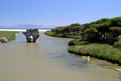Oude brug op rivier die tot het overzees in zonnig Spanje leidt Stock Foto