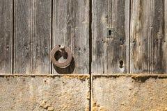 Oude bruine houten deur met een oude deurkloppers en een slot Stock Afbeelding