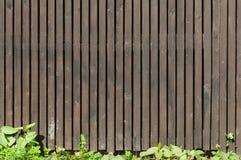 Oude bruine houten omheining met groen gras Stock Afbeelding