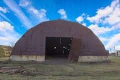 Oude bruine roestige metaalhangaar met open gebroken poorten onder een heldere blauwe hemel met witte wolken stock foto's