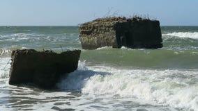 Oude bunker van tweede wereldoorlog in golven Strand van Oostzeekust in Wustrow stock footage