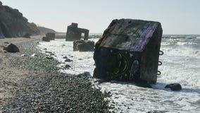 Oude bunker van tweede wereldoorlog in golven Strand van Oostzeekust in Wustrow stock videobeelden