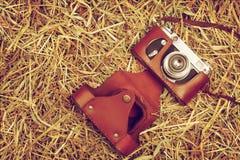 Oude camera met geval op hooi Stock Fotografie