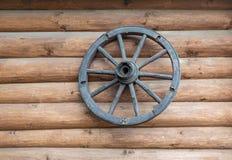 Oude cartwheel hangt op de muur van een logboekhuis royalty-vrije stock afbeeldingen