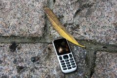 Oude cellphone op de vloer stock afbeeldingen