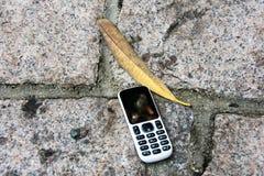 Oude cellphone op de vloer royalty-vrije stock fotografie