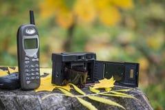 Oude cellulaire telefoon en filmcamera Mobiele telefoon van 90 ` s en camera van 80 ` s stock fotografie
