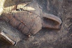 Oude ceramische kruik, amfora en menselijke die beenderen in de begrafenis tijdens archeologische uitgravingen wordt gevonden stock afbeelding