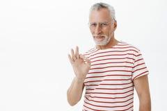 Oude charismatische en zelf-verzekerde mens die het koele en koele tonende o.k. gebaar en glimlachen tevreden bij camera blijven royalty-vrije stock foto's