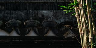 Oude Chinese textuur zwarte muur met bamboeinstallaties in Chinese tuin, Tuin met oude de bouwachtergrond royalty-vrije stock afbeeldingen