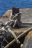 Oude cleat en een grote kabel dichtbij het overzees Stock Fotografie