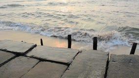 Oude concrete dijk met houten posten tegen de achtergrond van overzeese golven met een zonnige weg in de avond stock videobeelden