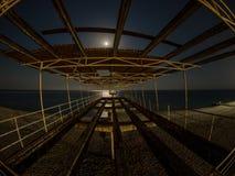 Oude concrete pijler op het strand bij nacht in het maanlicht stock fotografie