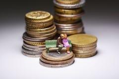 Oude dag zonder tekort aan geldconcept met hogere familiezitting op een bank boven stapels van muntstukken stock afbeeldingen
