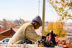 Oude Dame die Afrikaanse Curiosa op verkoop buiten Nelson Mandela ` s verkopen Royalty-vrije Stock Afbeelding