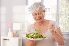 Oude dame die groene salade eten Stock Foto