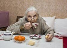 Oude dame het drinken thee Royalty-vrije Stock Afbeeldingen