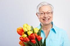 Oude dame met bloemen het glimlachen Stock Foto's