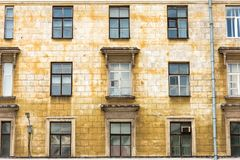 Oude de bouw vereisende reparatie in slechte voorwaardenvensters en balkons stock afbeelding