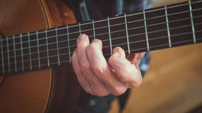 Oude de gitaarsnaar van mensenspelen stock foto