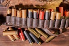Oude de jachtpatronen en patroongordel op een houten lijst stock fotografie