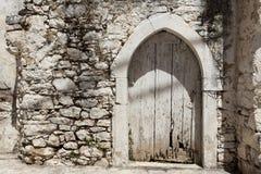 Oude deur in de steenmuren van de dorpshuizen Uitstekende achtergrond Stock Afbeeldingen