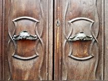 Oude deur met gepolijste metaalhandvatten en gebogen decoratie Stock Foto's