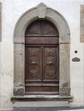Oude deur met gepolijste metaalhandvatten en gebogen decoratie Stock Afbeelding