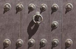 Oude deur met ijzerornamenten en deurkloppers stock afbeeldingen