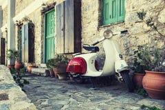 Oude die autoped door de muur in de lege straat van Karpathos wordt geparkeerd, royalty-vrije stock afbeelding