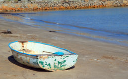 Oude die boot op een strand wordt verlaten Stock Afbeelding