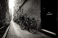 Oude die fietsen op een smalle straat in Amsterdam worden geparkeerd Royalty-vrije Stock Fotografie