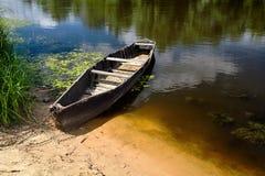 Oude die het roeien boot met ketting en hangslot bij groene de zomerbank wordt gebonden royalty-vrije stock foto's