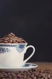 Oude die koffiekop met koffiebonen wordt gevuld Royalty-vrije Stock Afbeeldingen
